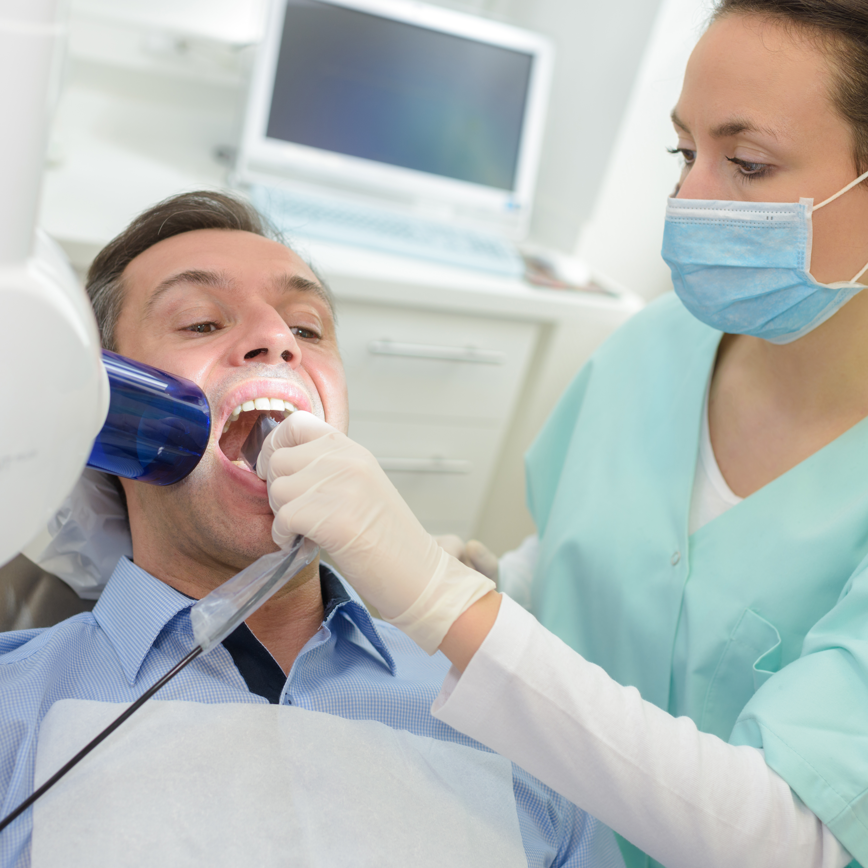 dentist doing digital xray in dentist office PEYMCLT 1